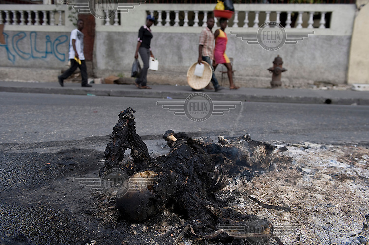 A dead body that had been lying in the streets for days has been burned to prevent the spread of disease, one week after an earthquake hit the country. .A 7.0 magnitude earthquake struck Haiti on 12/01/2010. Early reports indicated that more than 100,000 may have been killed and three million affected.