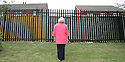 A teacher from Hazelwood Integrated Primary School, stands where a peaceline is due to be built inside the school grounds, keeping rival youths from the Whitewell Road area away from a small mixed housing estate of Old Throne Park. Photo/Paul McErlane.