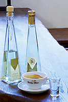 Triangular pyramid shaped Bottles of Loza and Travarica rakija grappa type grape spirit, a cup of espresso coffee and a glass of digestif alcohol. In the restaurant and wine bar at the winery. Podrum Vinoteka Sivric winery, Citluk, near Mostar. Federation Bosne i Hercegovine. Bosnia Herzegovina, Europe.