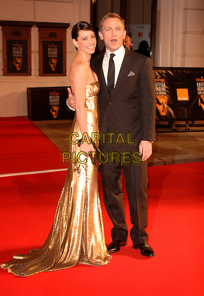 SATSUKI MITCHELL & DANIEL CRAIG.Red Carpet Arrivals at The Orange British Academy Film Awards (BAFTA's) held at the Royal Opera House, Covent Garden, London, England, February 11th 2007..full length strapless gold sequined dress.CAP/IL.©Ian Leonard/Capital Pictures