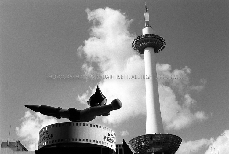 July, 2001--Kyoto, Japan..Astro Boty speeds through the sky in front of the Kyoto Tower.  The tower was meant to be a symbol of a new, modern and developed Kyoto. Built in 1964, city planners looked out over a city of traditional wood homes and tiled roofs and, like many cities in Japan, set about to destroy it...All photographs ©2003 Stuart Isett.All rights reserved.This image may not be reproduced without expressed written permission from Stuart Isett.
