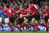 27/03/2004  -  RBS Six Nations Championship 2004 Wales v Italy.Iestyn Harris running through mid field, with support.   [Mandatory Credit, Peter Spurier/ Intersport Images].
