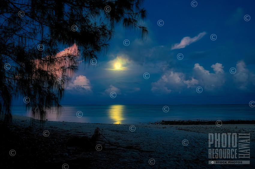 Full moon with the sun rising at Amuri Beach, Aitutaki Island, Cook Islands.