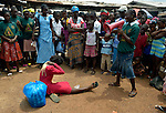 "Members of ""Daughters of the King,"" a girls' organization that carries out public education about HIV and AIDS, performs a drama in the market in Kakata, Liberia, focused on fighting the stigma and discrimination often associated with the disease. The group  is sponsored by the HIV/AIDS Program of the Lutheran Church in Liberia."