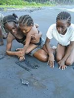 local children watch leatherback sea turtle hatchling, Dermochelys coriacea, run to sea, Dominica, West Indies, Caribbean, Atlantic