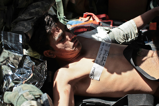 "An Afghan soldier is loaded onto a U.S. medical evacuation helicopter from the 101st Combat Aviation Brigade's ""Shadow Dustoff"" after being wounded in a bomb explosion in Zhari district, near Kandahar, Afghanistan. Sept. 16, 2010. DREW BROWN/STARS AND STRIPES"