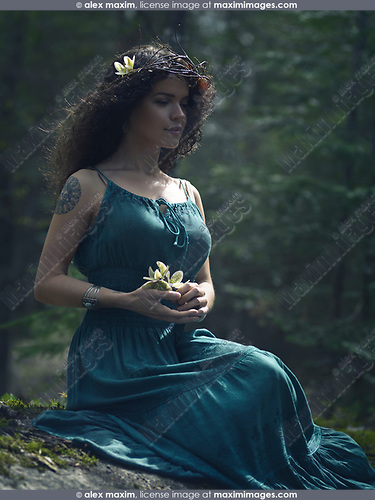 Artistic romantic portrait of a beautiful young woman in a green summer bohemian dress sitting in the nature with a wild flower in her hands, tattoo on her shoulder and a wreath made of dry tree branches on her head