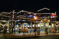 Shoppers head out into the evening to enjoy the many stores,art galleries and restaurants along Front street in historic downtown Lahiana,Maui.This photo is at the Wharf cinema center and t-shirt factory.