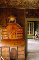 Hand-painted paper covers the walls of this study which has an elegant bureau next to the door