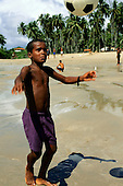 Itaparica Island, Bahia State, Brazil. Boy heading a football on the beach.