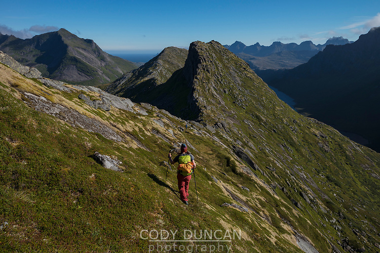 Female hiker descends ridge towards Nonstind mountain peak, Moskenesøy, Lofoten Islands, Norway