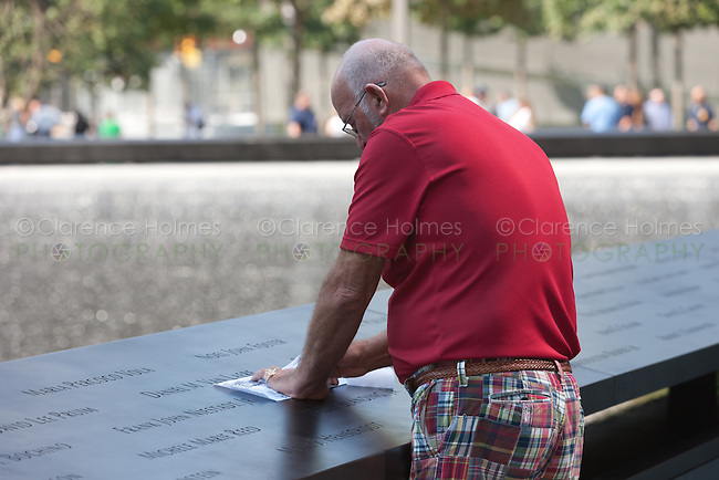 A visitor creates a rubbing of one of the names at the National 9/11 Memorial in New York City.