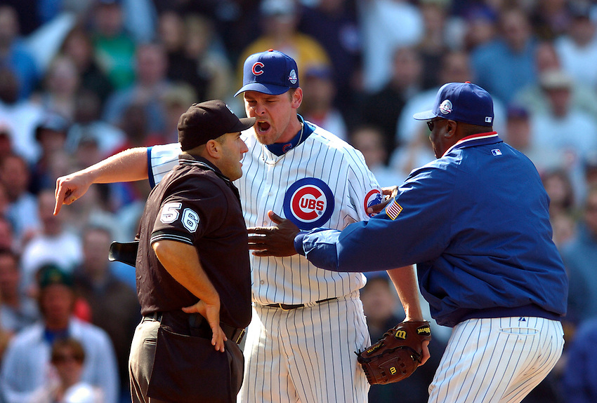 Cubs pitcher Kerry Wood(C) yells at home plate umpire Eric Cooper(L) as manager Dusty Baker(R) tries to intervene. Two batters earlier Wood was visibly upset after Cooper called a 3-2 borderline pitch for a ball. As Baker came to relieve Wood, the pitcher shouted to the umpire and then charged him after Cooper retorted. The inning started with the Cubs ahead 2-1 and lost 3-2.