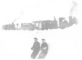 Two trainmen leaing against snowbank with engine with wedge pilot plow, flanger and second engine behind the bank.<br /> D&amp;RGW  Silverton Branch, CO  Taken by Duca, Frank J. - 1920