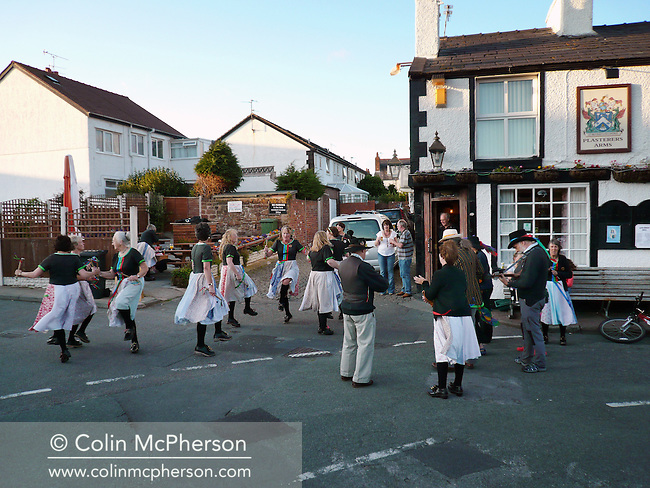 A group of dancers from Mockbeggar Morris performing outside the Plasterers public house in Hoylake, Wirral in north west England. Morris dancing in the region originated in the cotton mills of Lancashire and are danced in leather clogs with wooden soles. The traditional dancing was performed to a musical accompaniment including instruments such as  malodeon, concertina, violin and mandola.