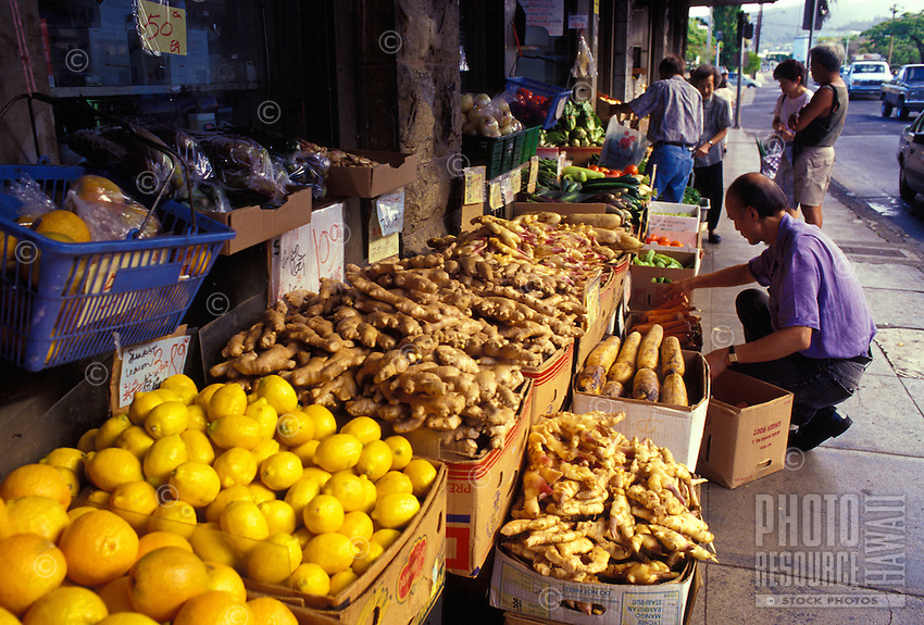 Shoppers browsing the Chinatown food markets, with fresh fruit and vegetable displays spilling onto the sidewalk, near King and Mauna Kea Streets, Downtown Honolulu