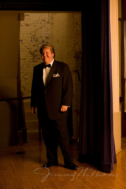 An opera singer stands backstage with a smile on his face before a performance.