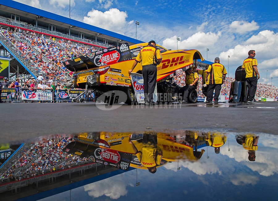 Sep 20, 2015; Concord, NC, USA; Crew members stand alongside NHRA funny car driver Del Worsham as they reflect in a puddle of water during the Carolina Nationals at zMax Dragway. Mandatory Credit: Mark J. Rebilas-USA TODAY Sports
