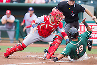 Hagerstown Suns catcher Spencer Kieboom (20) can't handle the throw as Juan Avila (19) of the Greensboro Grasshoppers slides into home plate at NewBridge Bank Park on May 20, 2014 in Greensboro, North Carolina.  The Grasshoppers defeated the Suns 5-4. (Brian Westerholt/Four Seam Images)