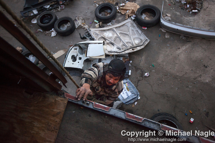 QUEENS, NY -- OCTOBER 25, 2013:  Giovany Sadano climbs into an abandoned shipping container in Willets Point, where he sometimes sleeps, on October 25, 2013 in Queens, NY.  PHOTOGRAPH  BY MICHAEL NAGLE FOR THE NEW YORK TIMES