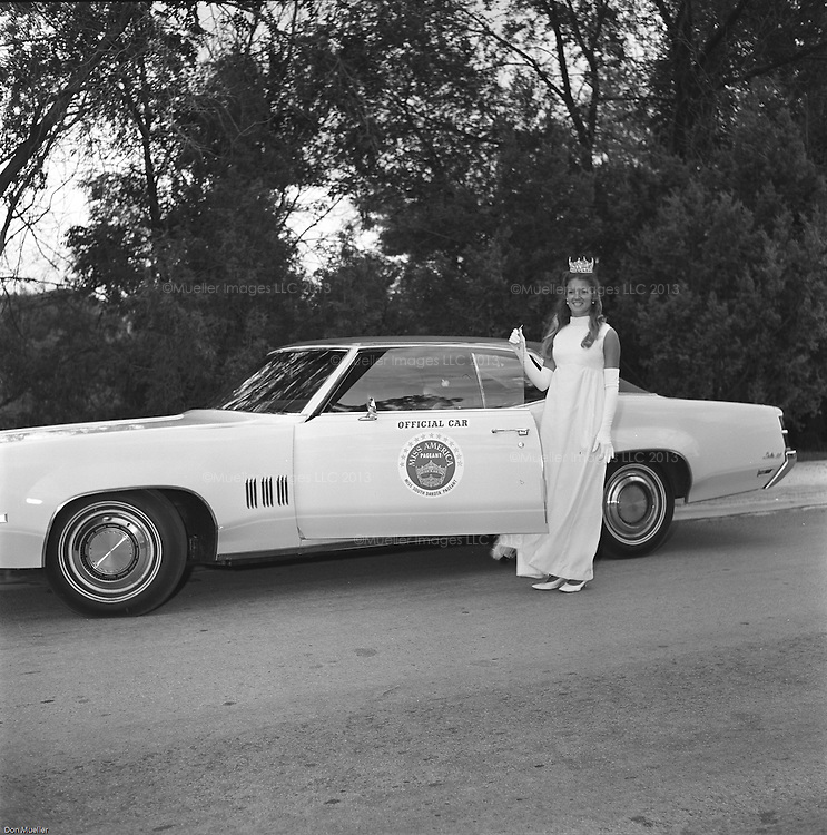 In 1970 Mary Harum (now Mary Hart) competed in the Miss America Pageant as Miss South Dakota and finished top ten. Don Mueller who produced the Miss South Dakota Pageant took these photographs of Mary in her crown and cape with the official car by the United Church in Hot Springs, South Dakota. Other images show Mary visiting the following year, participating in the Miss South Dakota Pageant and crowning her successor, Susan Inman.