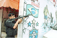 Daily life, violence at Complexo do Alemão slum ( favela do Alemao ), Rio de Janeiro, Brazil. Poverty and drug traffic. Police action. Graphites related to World Cup ( Ronaldinho, soccer player ) and Osama Bin Laden.