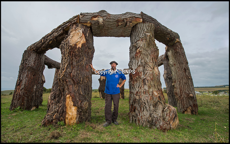 BNPS.co.uk (01202 558833)<br /> Pic: PhilYeomans/BNPS<br /> <br /> Amateur archaeologist Charlie Newman at his massive Woodhenge, built of Monterey pine.<br /> <br /> Timberrrrr..35 ton Woodhenge is given the chop by local council.<br /> <br /> A pub landlord who was inspired to build a wooden version of Stonehenge out of 35 tonnes of felled trees has been given six weeks to axe the impressive structure by officials.<br /> <br /> Charlie Newman, 49, has erected a 12ft tall circle made out of huge butts of Monterery pine trees on a field he owns near to his pub in the village of Worth Matravers, Dorset.<br /> <br /> The installation is made from 12, 10ft tall 'plinths' that each weigh about two-and-a-half tonnes and are topped with 8ft long sections of trunk.