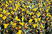 Rio de Janeiro, Brazil. Carnival samba school; mass of people in red and yellow feathers.
