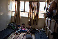 Children play at their temporary home in a converted classroom at a secondary school that has become a shelter for displaced persons. The school houses 65 families, mostly made of up of women and children.