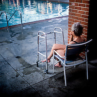 73 year old Margo Bouer sits before an Aquadette practice at Laguna Woods, California. Margo suffers from severe MS, but says her nausea and shaking almost disappear when she is in the swimming pool. She has been with the Aquadettes for 16 years. The Aquadettes are a group of women ageing from their early 60s upwards who meet to practice synchronised swimming. Every year, they practice together, they make costumes together, they swim together, and at the end, they perform together.