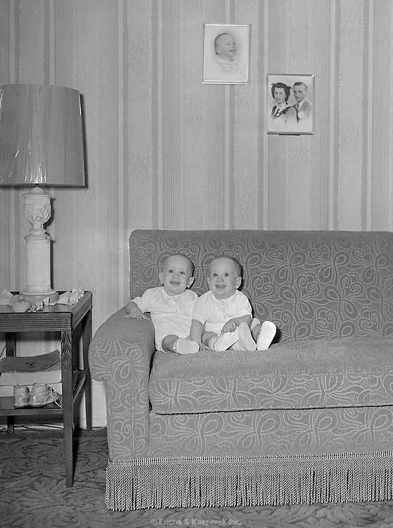 Twin babies are photographed on a sofa. Circa 1950.