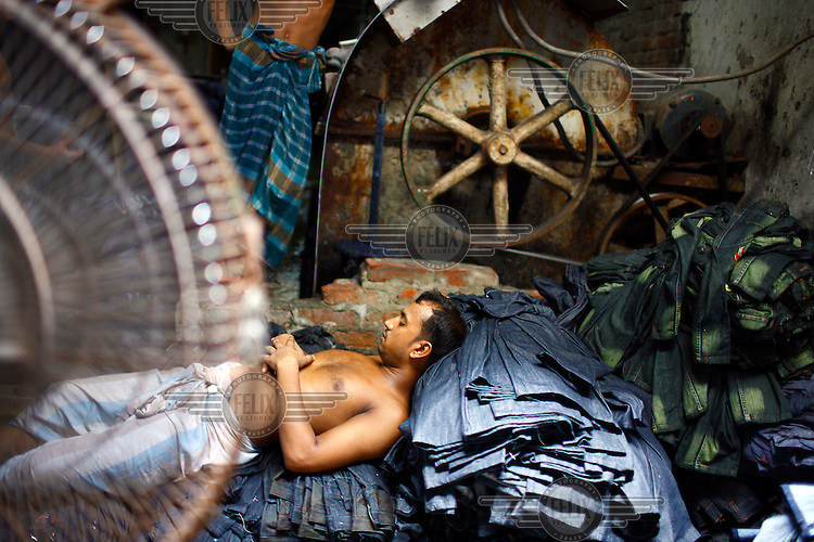 A worker sleeps on top of a pile of newly made jeans in a small garmnet factory.