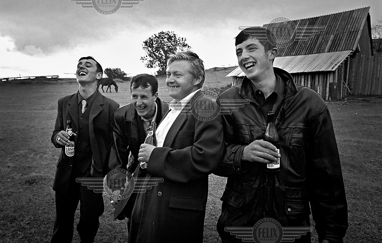 Men laugh together whilst drinking beer at the end of a wedding party in Cluj.