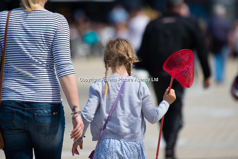 Aberystwyth Wales Uk, Sunday 08 May 2016<br /> Pictured: People walk on the promenade<br /> UK Weather : As temperatures reach the upper 20's centigrade in parts of Britain, people enjoy the warm May sunshine in Aberystwyth on the Cardigan Bay coast in West Wales.
