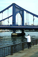 """Japanese fisherman along the banks of the Sumida River by Kiyosubashi Bridge.  The Kiyosu Bridge, built in 1928 after the model of the Deutz Suspension Bridge of Cologne, links Kiyosu with Nihonbashi. The Sumida River or Sumida-gawa as it is known in Japanese, is a river which flowing through Tokyo. It branches from the Arakawa River and flows into Tokyo Bay. Its tributaries include the Kanda and Shakujii rivers. What is now known as the """"Sumida River"""" was previously the path of the Arakawa River, however towards the end of the Meiji period the rivers were diverted from the main flow of the Arakawa to prevent flooding."""