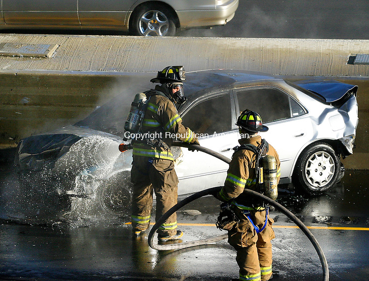 WATERBURY, CT. 31 OCTOBER 01_NEW_103108DA01.jpg-Firefighters extinguish a car that was involved in a multi car accident shutting down I84 east at exit 25a in Waterbury Friday.  REPUBLICAN/AMERICAN  Darlene Douty