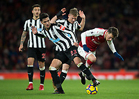 Mikel Merino of Newcastle United tackles Mesut Ozil of Arsenal during the Premier League match between Arsenal and Newcastle United at the Emirates Stadium, London, England on 16 December 2017. Photo by Vince  Mignott / PRiME Media Images.