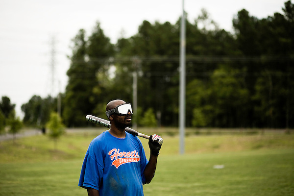 July 25, 2008. Durham, NC.. Started over 30 years ago, Beep Ball is baseball for the visually impaired. Played with an oversized softball that beeps, and bases that also make sound, the game has allowed people with varying degrees of visual impairment to participate in a team sport. All players are required to wear blacked out masks, to equalize the impairment and if the fielding team gets control of the ball before the hitting player reaches the base, an out is recorded. If the hitting player reaches the base first, a run is scored. There are only 2 bases, one to the left and one to the right, and the hitting player hears a tone after the hit is made, to add to the difficulty, telling them which base to run to.. Marlin Stover, of the Charlotte Hornets, waits for a passing truck to go by so they can resume play.