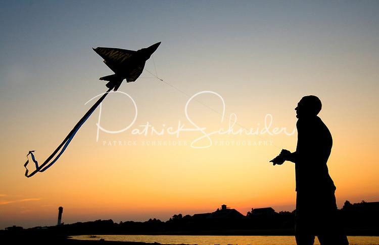 A man flies his kite at sunset.