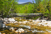 Looking downstream at Thoreau Falls Trail bridge in the Pemigewasset Wilderness of Lincoln, New Hampshire. This wooden bridge, at North Fork junction, crosses the East Branch of the Pemigewasset River. It was damaged during Tropical Storm Irene in 2011, and there is now a one-person weight limit.