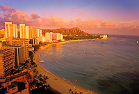 Glowing sunset shot of Waikiki beach and hotels, curving in a semi-circle with majestic Diamond Head ringed with dusty pink clouds and overlooking the serene waters of the Pacific.