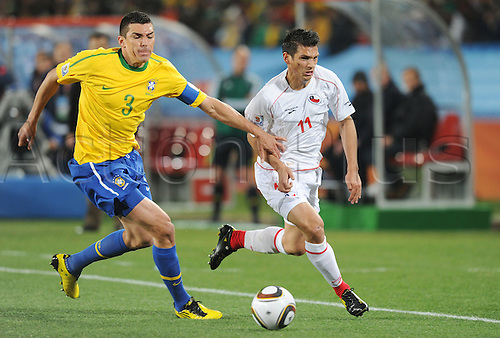 Lucio of Brazil fights for the ball with Mark Gonzalez of Chile during the 2010 FIFA World Cup soccer match between Brazil and Chile at Ellis Park Stadium on June 28, 2010 in Johannesburg, South Africa.