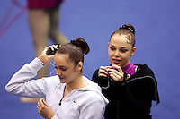 (L-R) Anna Bessonova and Galina Shyrkina of Ukraine share the same mp3 player and listen to the soundtrack to their gala exhibition at San Francisco Invitational on February 11, 2006. Bessonova won All-Around competition. (Photo by Tom Theobald)