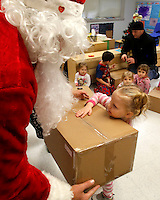 NWA Media/DAVID GOTTSCHALK - 12/19/14 - Kinley Cunningham receives a gift from Santa Claus in the three to five year old class of Marty Fink at Bentonville Public Schools Childcare Enrichment Services Building Bridges Friday December 19, 2014 in Bentonville.  Sponsored by United Way Gift of Kindness Warehouse, the children at the school read holiday stories, enjoyed hot chocolate and received a visit from Santa Claus who delivered gifts.