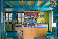 This cheerful kitchen has a yellow and turquoise painted ceiling with a turquoise floor to match, while built-in storage units are painted in green and the stove is a deep pink