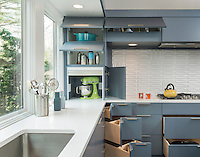 A contemporary kitchen with grey blue cabinets. A clever arrangement of drawers allows plenty of storage. A textured splashback is set behind a gas hob.