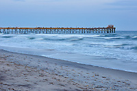 View of fishing pier and ocean waves at Atlantic Beach shortly after sunset