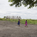 Uganda - Palorinya Refugee Camp - South Sudanese refugee girls pass by a tent that was destroyed by other refugees. These petty crimes are often committed by former child soldiers who face more difficulties in overcoming their trauma and adapting to a new life.