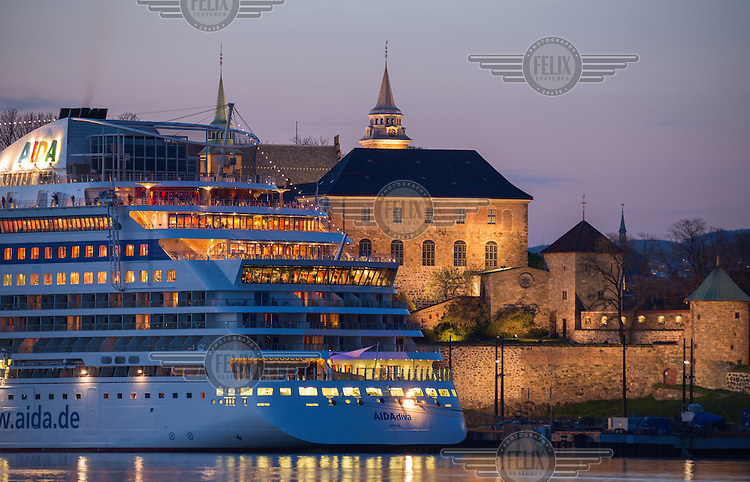 Cruise ship in front of Akershus fortress  in the centre of Oslo. The  medieval castle that was built to protect Oslo, construction  believed to have started late 1290s, by King Haakon V.  As seen from the island Hovedøya. The fortress is one of the city's most important tourists attractions.