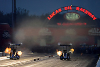 Sept. 1, 2012; Claremont, IN, USA: NHRA top fuel dragster driver Antron Brown (left) races alongside J.R. Todd during qualifying for the US Nationals at Lucas Oil Raceway. Mandatory Credit: Mark J. Rebilas-